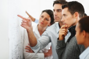 Group of business people looking at a chart put up on the wall
